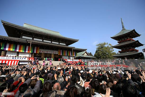 Visitors reach out for the beans thrown by sumo wrestlers, actors and actresses during a bean-scattering ceremony at Shinshoji Temple on February 3,...