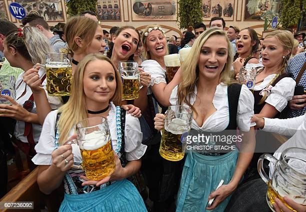 Visitors react as a waitress carries the beer mugs during the opening of the Oktoberfest beer festival in a festival tent at the Theresienwiese in...