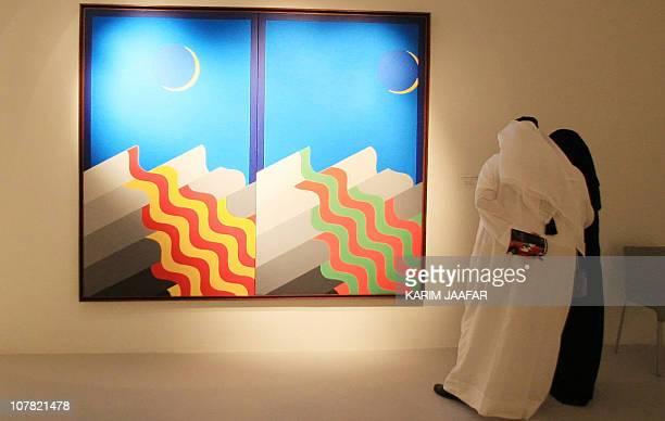 Visitors read information about a painting by Arab artist Mohammed elMelehi during a tour of Doha's new Arab Museum of Modern Art which opened to the...
