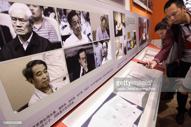 Visitors read the statements of repentance written by some of the fallen top corrupted officials while the pictures of six highest ranking corrupted...