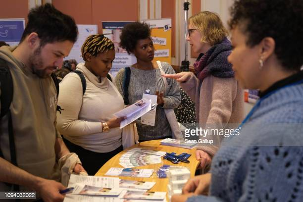 Visitors receive information at the stand of a local job training center at a jobs fair for refugees that promotes training programs and jobs in the...