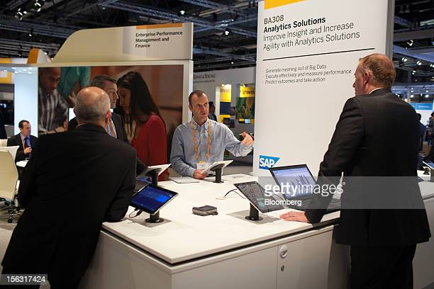 Visitors receive information from a specialist at a display of tablet devices on an SAP AG analytics solutions pavilion on the opening day of the...