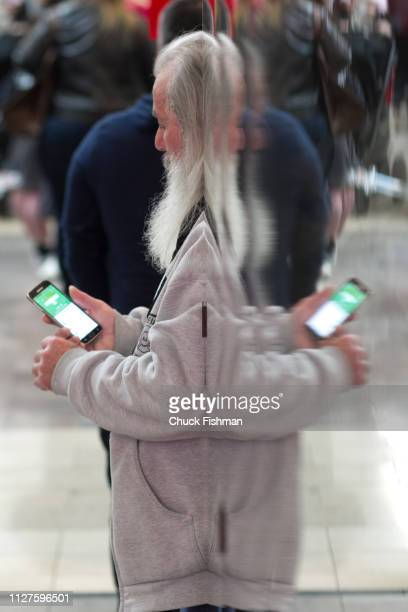 A visitor's reflection upon a mirrored wall makes a double image as he checks his cell phone at The Chocolate Expo at Garden State Plaza Mall Paramus...