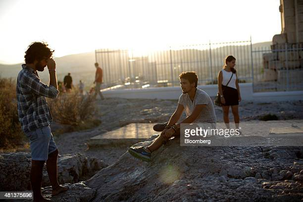 Visitors relax after watching the sun set from the top of Philopappos hill in Athens Greece on Sunday July 19 2015 German Chancellor Angela Merkel...