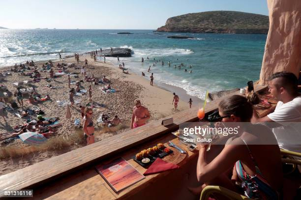 Visitors relax at Sunset Ashram at Cala Conta beach on the island of Ibiza on August 8 2017 near Es Canar Spain Ibiza is a popular tourist destination