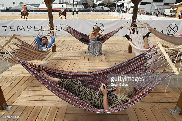 Visitors relax next to the Tom Tailor polo field at the 2012 Bread & Butter fashion trade fair at former Tempelhof Airport on July 6, 2012 in Berlin,...