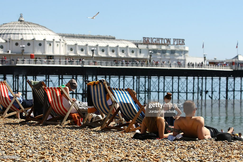 Visitors relax on the beach in front of Brighton Pier on May 6, 2013 in Brighton, England. Visitors have flocked to Brighton Beach as the Met Office predict the May Day Bank Holiday to be the hottest day of the year so far.