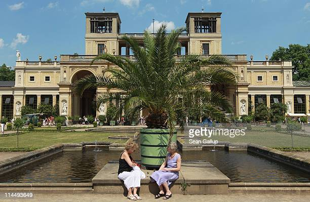 Visitors relax under a palm tree outside the Orangerie at Sanssouci Park on May 22 2011 in Potsdam Germany Every year workers wheel out the several...