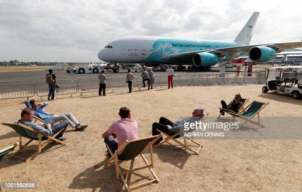 Visitors rest in deckchairs near an Airbus A380 passenger aircraft operated by HiFly at the Farnborough Airshow south west of London on July 19 2018