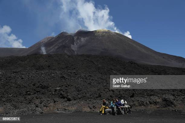 Visitors rest next to hardened lava below the peak of Mount Etna on the island of Sicily on May 28 2017 near Catania Italy Mount Etna is among the...