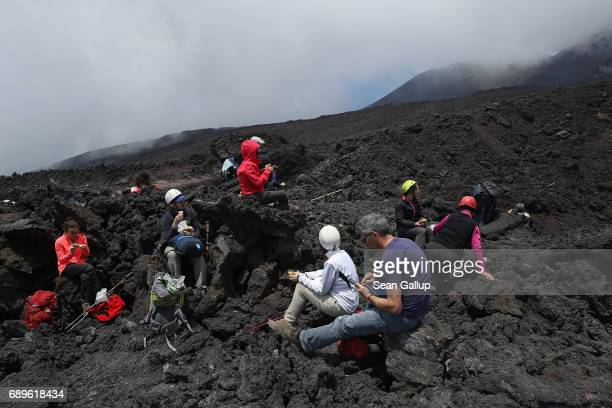 Visitors rest while hiking on a hardened lava stream near the peak of Mount Etna on the island of Sicily on May 28 2017 near Catania Italy Mount Etna...