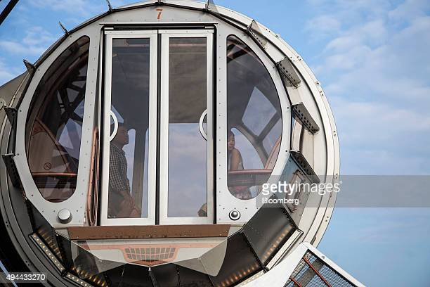 Visitors ride a passenger pod of the Golden Reel ferris wheel at Studio City casino resort developed by Melco Crown Entertainment Ltd in Macau China...