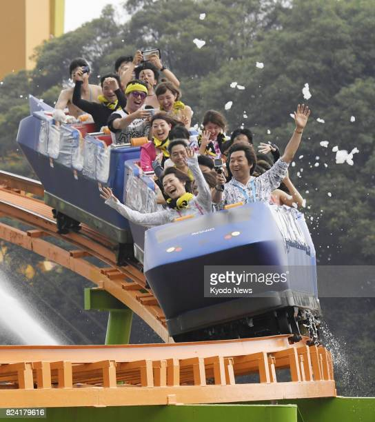 Visitors ride a roller coaster with its seats filled with bubbles made from hotspring ingredients at Beppu Rakutenchi amusement park in Beppu Oita...