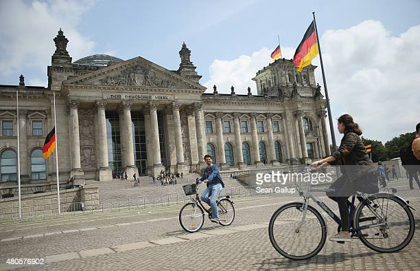 Visitors ride bicycles past the Reichstag seat of the German parliament the Bundestag on July 13 2015 in Berlin Germany Earlier in the day Greek and...