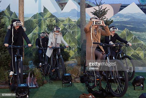 Visitors ride bicycles with the virtual reality headmounted Samsung Gear VR powered by Oculus at 'Le Grand Palais' on December 15 2016 in Paris...