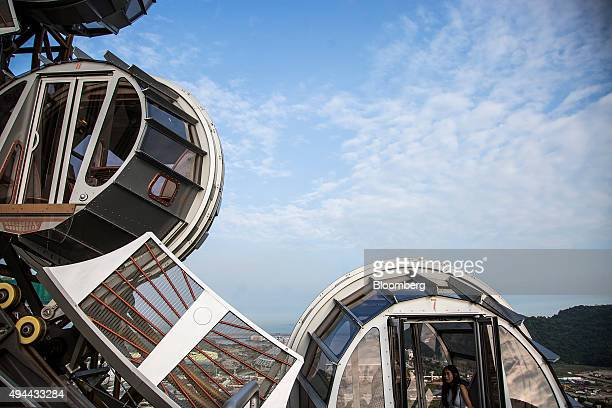 Visitors ride in a passenger pod of the Golden Reel ferris wheel at Studio City casino resort developed by Melco Crown Entertainment Ltd in Macau...