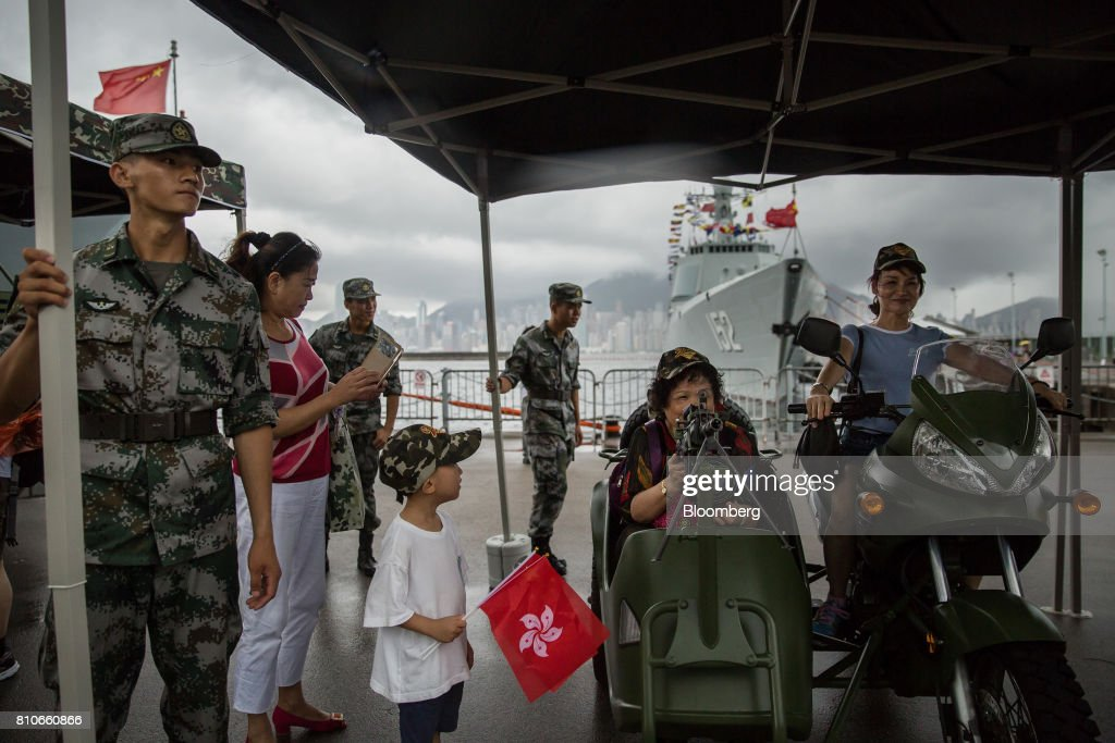 Visitors ride on a People's Liberation Army (PLA) motorcycle as they pose for photographs during an open day at the Ngong Suen Chau Barracks in Hong Kong, China, on Saturday, July 8, 2017. China's bid to display some soft power in Hong Kong-- with a visit by the country's first aircraft carrier -- has also showcased its heavy-handed approach to security. Photographer: Billy H.C. Kwok/Bloomberg via Getty Images