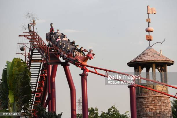 Visitors ride on a rollercoaster at the Universal Studios Singapore amusement park at Resorts World Sentosa in Singapore on December 3, 2020.