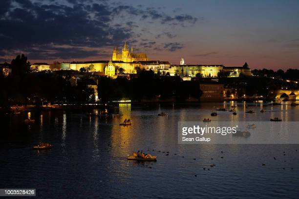 Visitors ride on paddle boats at night on the Vltava River as Prague Castle stands behind on July 20 2018 in Prague Czech Republic Prague is among...