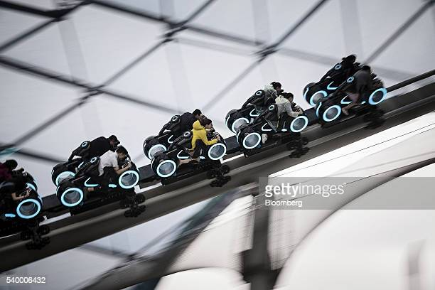 Visitors ride on the Tron Lightcyle Power Run rollercoaster at Walt Disney Co's Shanghai Disneyland theme park during a trial run ahead of its...