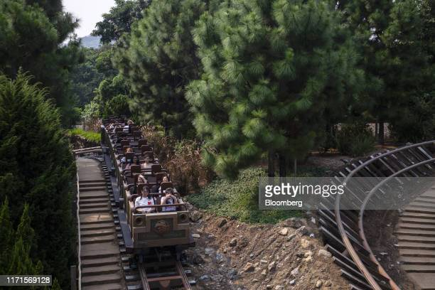 Visitors ride the Big Grizzly Mountain Runaway Mine Cars roller coaster at Walt Disney Co's Disneyland Resort in Hong Kong China on Friday Sept 27...