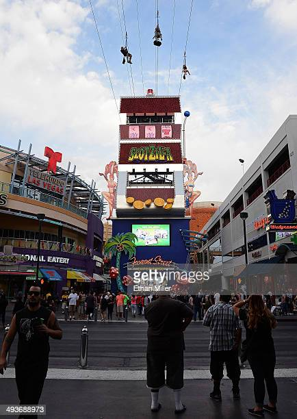 Visitors ride the SlotZilla zip line attraction at the Fremont Street Experience on May 24 2014 in Las Vegas Nevada