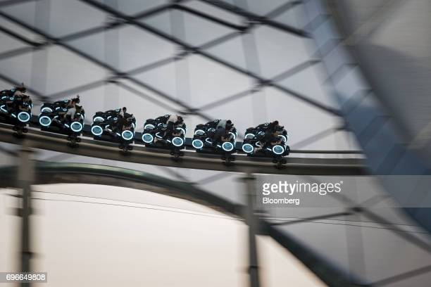 Visitors ride the TRON Lightcycle Power Run roller coaster attraction during the oneyear celebration of Walt Disney Co Shanghai Disneyland resort at...