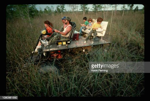 Visitors ride through the Everglades in a fourwheeldrive swamp buggy Broward County Florida