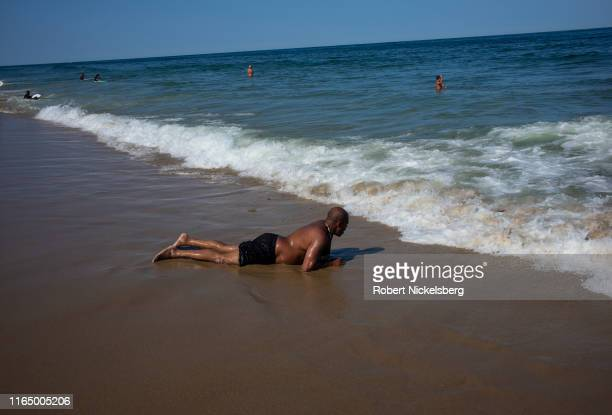 """Visitors ride waves along Cape Cod""""u2019s Nauset Beach in Orleans, Massachusetts on July 25, 2019. Located 90 miles southeast of Boston, Orleans is..."""