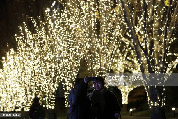 Visitors, right, take a selfie photograph in front of illuminated trees ahead of Christmas at the Tokyo Midtown complex in Tokyo, Japan, on...