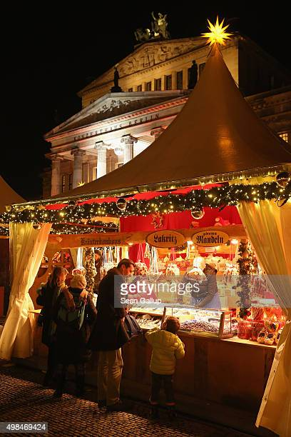 Visitors sample sweets at a stall at the annual Christmas market at Gendarmenmarkt on its opening day on November 23 2015 in Berlin Germany Christmas...