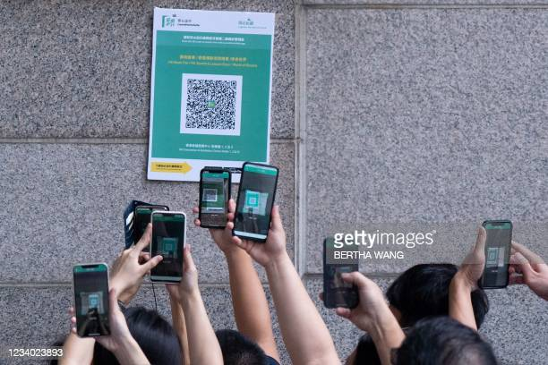 """Visitors scan a QR code for the Hong Kong government's """"Leave Home Safe"""" app to trace people in the advent of any Covid-19 outbreaks, as they queue..."""