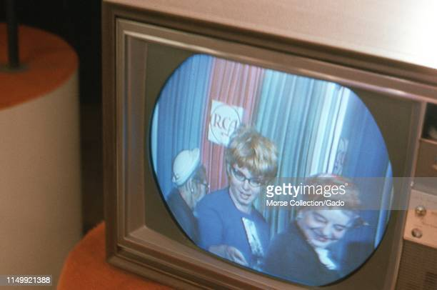 Visitors see themselves broadcast in color for the first time from monitor sets lining the entrance to the Color Television Communications Center...