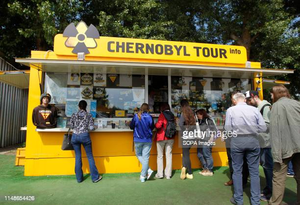 Visitors seen stand next to a shop with Chernobyl souvenirs on the Dytyatky checkpoint at the Chernobyl exclusion zone in Pripyat The HBO television...