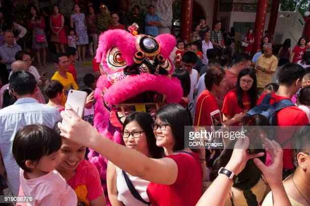 Visitors seen taking photos and selfie during the lion dance performance at the Thean Hou Temple on the first day of Chinese New Year to see the lion...