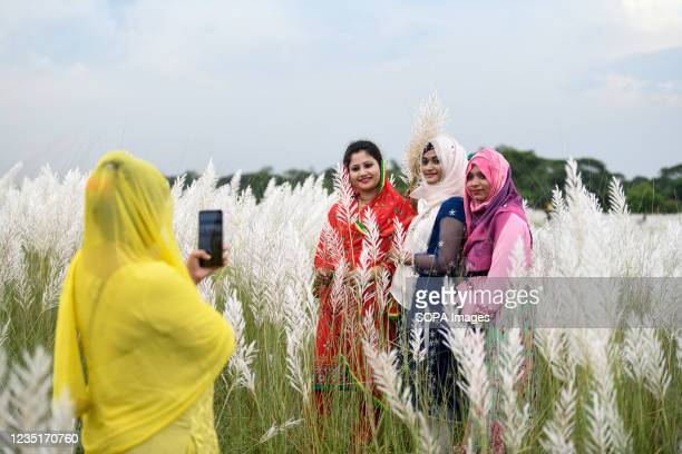 Visitors seen taking photos in a Kans grass field at Sarighat, on the outskirts of Dhaka. Kans grass field in Sarighat is one of the popular...