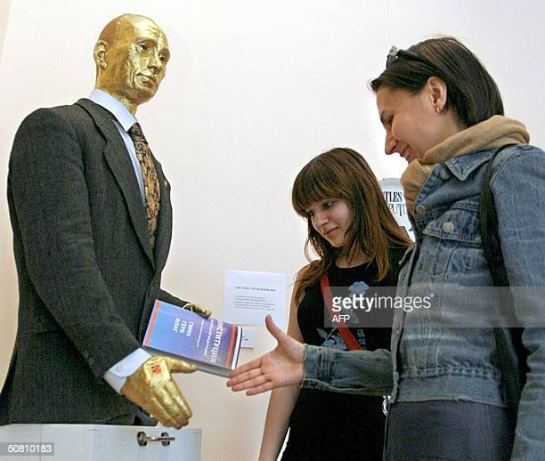 Visitors shake hand with a gold covered sculpture of the Russian President Vladimir Putin and receive an answer 'I love You' in 'Anna Akhmatova'...