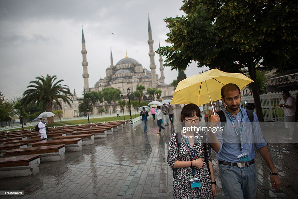 Visitors shelter from the rain beneath umbrellas near the Blue Mosque, also known as the Sultan Ahmed, in Istanbul, Turkey, on Friday, June 14, 2013. The law forbids the sale of alcohol at night and near schools and mosques, going against the secular traditions of the Muslim-majority country of 74 million, where many people drink and women often choose not to cover their hair. Photographer: Lam Yik Fei/Bloomberg via Getty Images