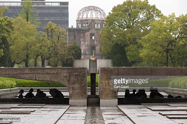 Visitors shelter from the rain under the Peace Flame as they visit the Memorial Park and the nearby Hiroshima Peace Memorial Museum on April 21 2016...