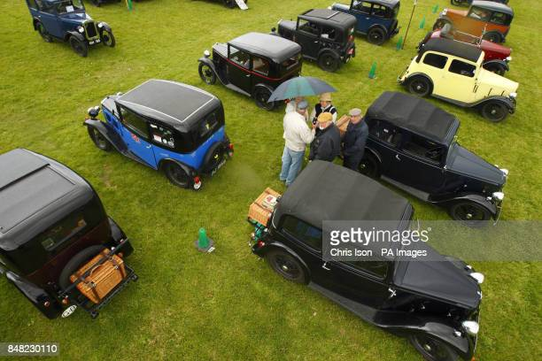 Visitors shelter under an umberella during a shower at the 50th Austin Seven rally at the National Motor Museum in Beaulieu Hampshire