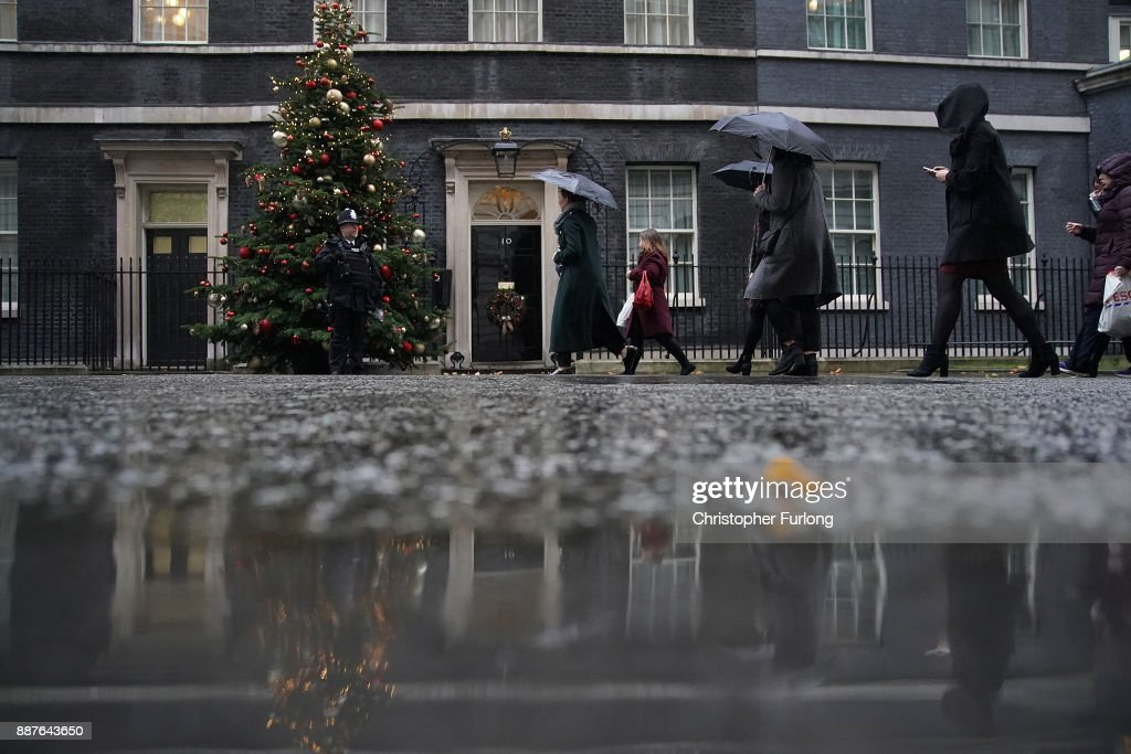 Visitors shield themselves from the rain outside 10 Downing St on December 7, 2017 in London, England. The British Government continues to work out a deal on the matter of the Ireland border before Brexit negotiations with the EU can continue.