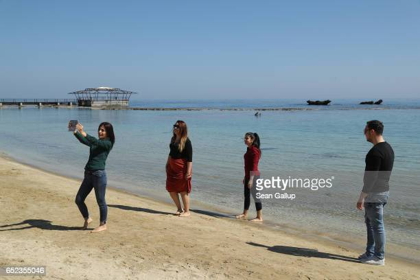"""Visitors shoot a selfie on a public beach in the Turkish Republic of North Cyprus only a few steps away from the """"Forbidden Zone"""" of Varosha district..."""