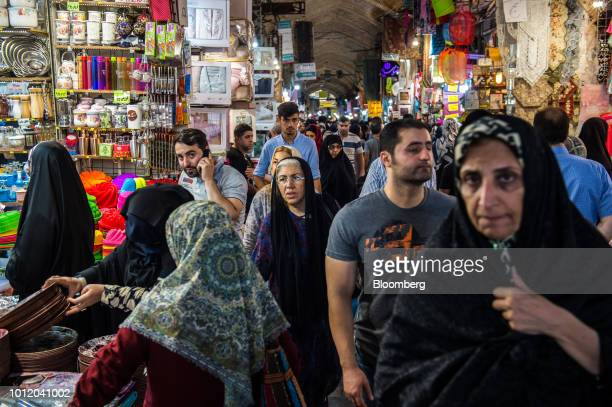 Visitors shop for goods at retail stores lining an arcade inside the Grand Bazaar in Tehran Iran on Monday Aug 6 2018 Irans central bank acting on...