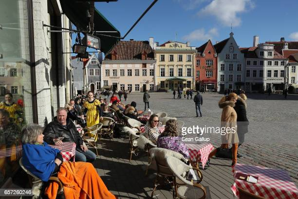 Visitors sit at an outdoor cafe on Town Hall Square in the historic city center on March 24 2017 in Tallinn Estonia Tallinn's old town escaped...