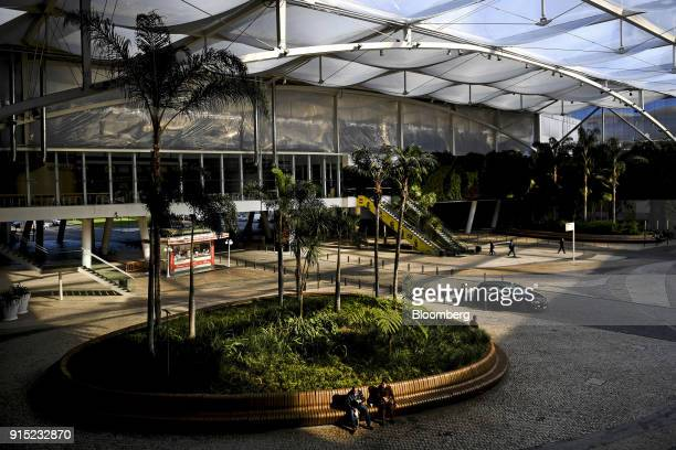 Visitors sit beside a planted area in the courtyard at the Dolce Vita Tejo shopping mall operated by AXA Real Estate Investment Managers SGR SpA in...