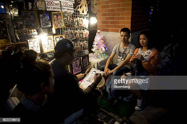 Visitors sit for a caricaturist at Asiatique The Riverfront openair mall in Bangkok Thailand on Friday Dec 18 2015 Thai economic indicators have...