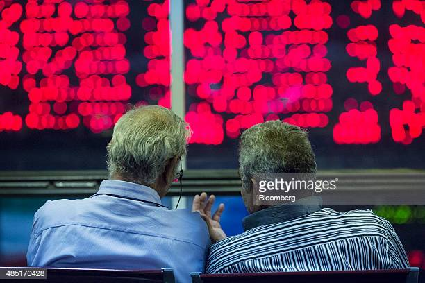 Visitors sit in a viewing area and look at financial information displayed on digital screens at the Tehran Stock Exchange in Tehran Iran on Monday...