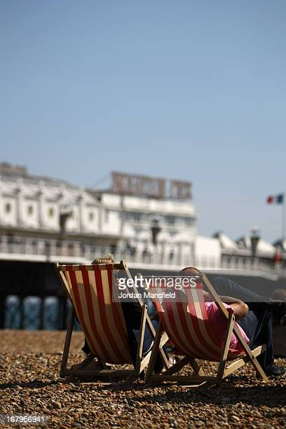 Visitors sit in deck chairs in front of Brighton Pier on May 3 2013 in Brighton England Southern England has enjoyed some warm and sunny weather...