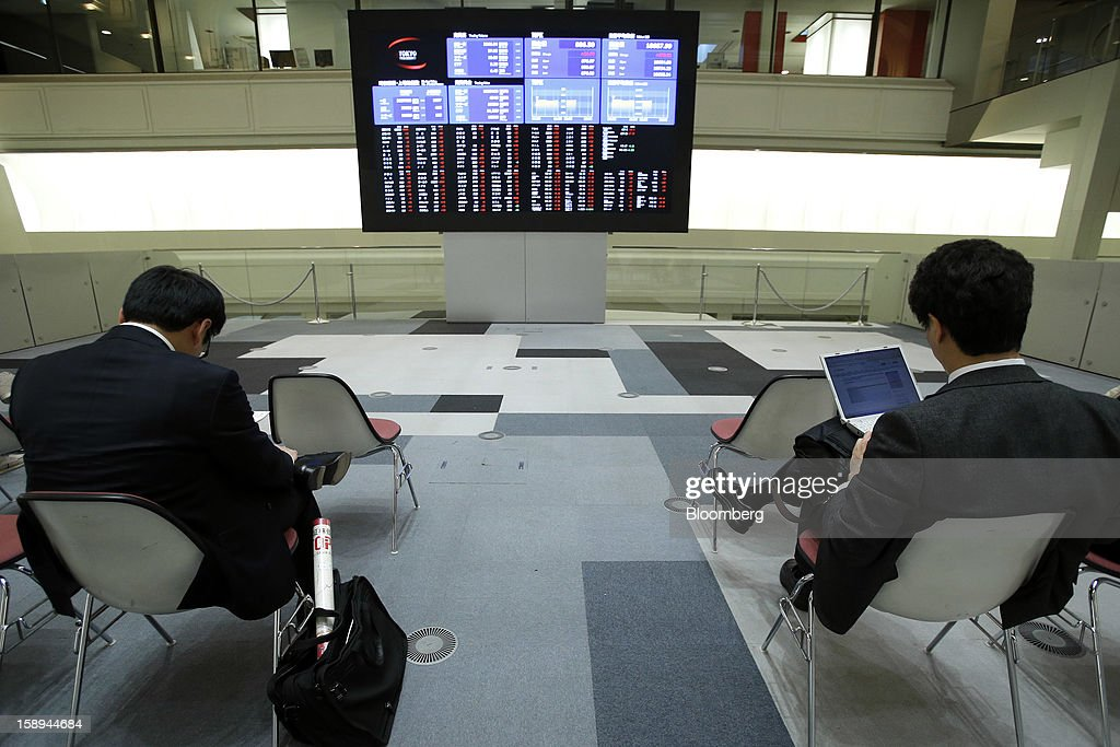 Visitors sit in front an electronic board displaying the Nikkei 225 Stock Average figure, top right, and share prices at Japan Exchange Group Inc.'s Tokyo Stock Exchange (TSE) on the first trading day of the year in Tokyo, Japan, on Friday, Jan. 4, 2013. Japan Exchange, created by the merger of Japan's two biggest bourses, fell in its trading debut on the Tokyo Stock Exchange. Photographer: Kiyoshi Ota/Bloomberg via Getty Images