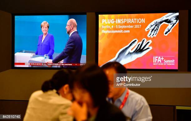 Visitors sit in front of a television set showing the tvdebate between German Chancellor and leader of the conservative Christian Democratic Union...